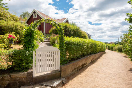 Photo for image of Narrow gravel lane beside red and white traditional allotment cabin with picket fence and flowers. Location Karlskrona in Sweden. - Royalty Free Image