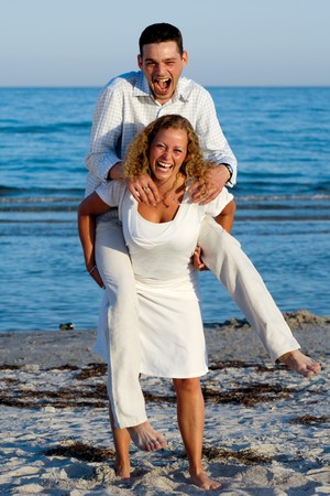 A happy woman and man having fun on beach.