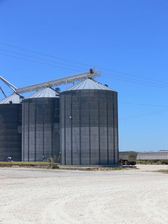 A photograph of several metal grain silos with a blue sky in the background.