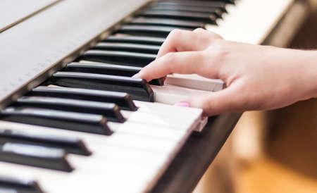 Foto de Hands of a young girl playing the piano, close-up. - Imagen libre de derechos