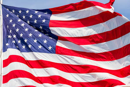 Photo pour Large beautiful American flag waving in the wind, with vibrant red white and blue colors, filling the frame. - image libre de droit