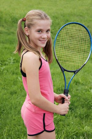 Happy teenage girl in sport outfits with tennis racket on green grass background