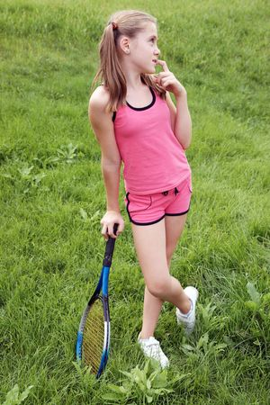 Happy preteen girl in sport outfits with tennis racket on green grass background