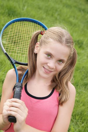 Happy teenage girl in sport outfits holding tennis racket on green grass background outdoors