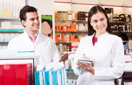 Pharmacist woman writes in a notebook. male pharmacist smiling while looking at her