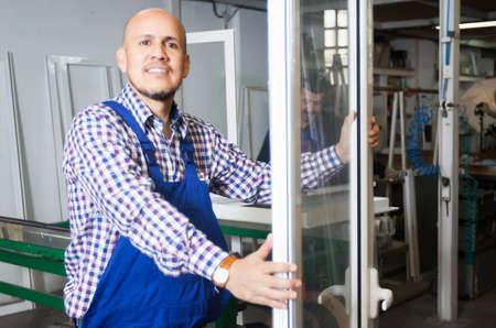 Photo pour Satisfied manager approving employee work at PVC windows factory - image libre de droit