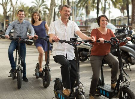 Photo for group of friends of tourists of different generations enjoy a ride on electric scooters - Royalty Free Image