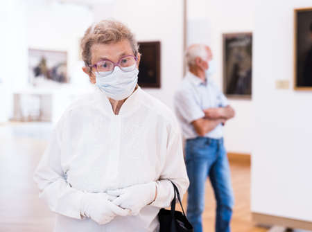 Photo pour mature woman in mask protecting against covid examines paintings on display in hall of art museum - image libre de droit