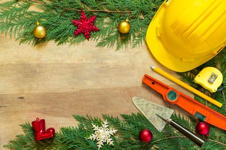 Photo pour Protective helmet, mason tools  and Christmas decorations on wooden background - image libre de droit