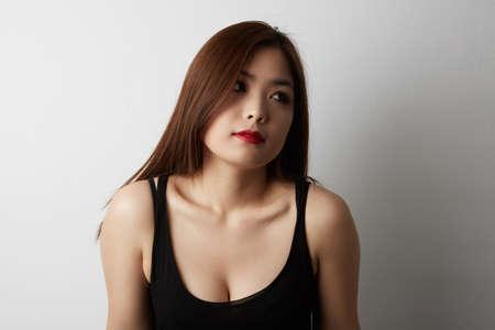 Foto de Beautiful asian woman with long hair posing in studio on black background. Isolated. - Imagen libre de derechos