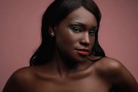 Photo for Portrait of young black woman posing in the studio, with glittery make-up. - Royalty Free Image
