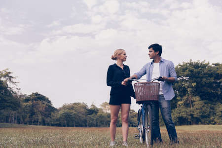 Foto per Happy young couple going for a bike ride on a sunny day in the park. - Immagine Royalty Free