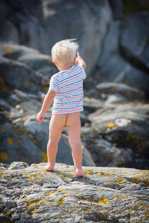 Photo for Little guy shows his butt and stands barefoot on a hot rock. - Royalty Free Image