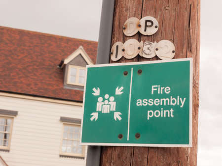 a green sign outside on a wooden pole saying fire assembly point fire warning