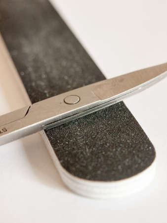 a pair of closed scissors resting on a nail file up close