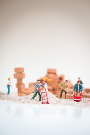 Photo pour Miniature workmen doing construction work on a cloudy day with the overcast sky like background  - image libre de droit