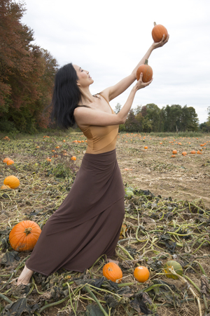 Photo for Adult woman dancer dressed in earth tones, standing in a farm field, reaching up with pumpkins in her hands, in Ellington, Connecticut. - Royalty Free Image