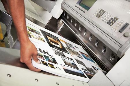 Photo pour Hand man working in offset printing cut machine during production - image libre de droit