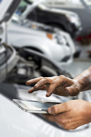 mechanic man hands whit computer. Cars in garage prepared for repair.