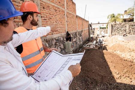 Photo pour Engineer and master builder reviewing details of construction in progress. - image libre de droit