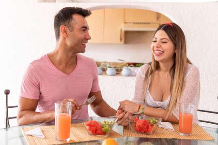 Foto de Happy married couple having breakfast fruits and vegetables in the dining room of their house. - Imagen libre de derechos