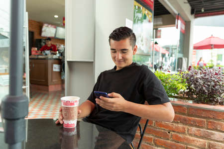 Photo pour Smiling and handsome young man drinking coffee in the mall with his cellphone - image libre de droit
