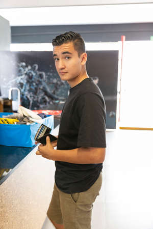 Photo pour Smiling and handsome young man buying tennis for football. difficult decisions - image libre de droit