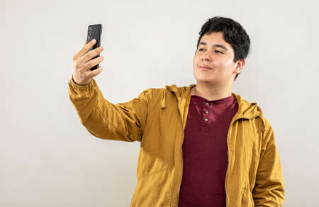 Photo pour Expression session. Young man taking selfies on his cell phone with different facial expressions - image libre de droit
