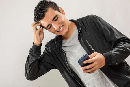 Photo pour Expression session. Young man watching his cell phone with different facial expressions - image libre de droit