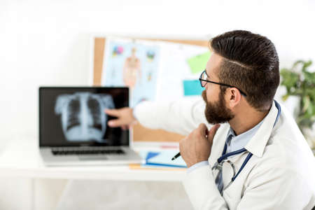 Photo pour Healthy and happy doctor with stetoscope on his office showing the diagnosis - image libre de droit