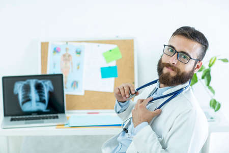 Photo pour Healthy and happy doctor with stetoscope on his office - image libre de droit
