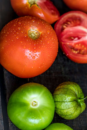 Photo pour Texture detail of a green tomatos and tomatoes in a wood table - image libre de droit