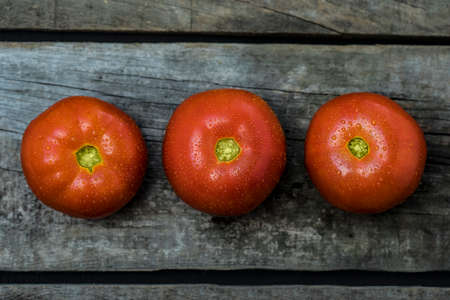 Photo pour Texture detail of a red tomatos in line over wood table - image libre de droit