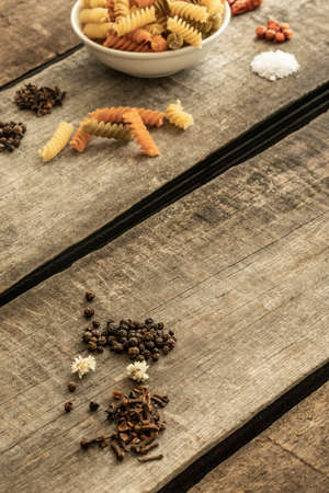 Photo pour Detail of pasta on a deep dish and other ingredients for sauce on a wooden table - image libre de droit