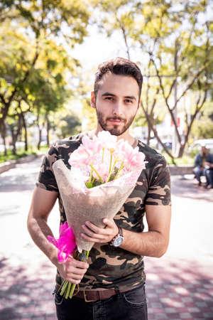 Foto de Young man handing flowers pink tulips to his girlfriend in the park. - Imagen libre de derechos