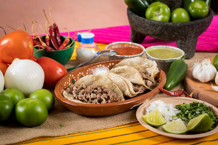 Photo pour Tacos of roast beef. Typical Mexican food of Guadalajara, rustic table full of sauces and vegetables. - image libre de droit