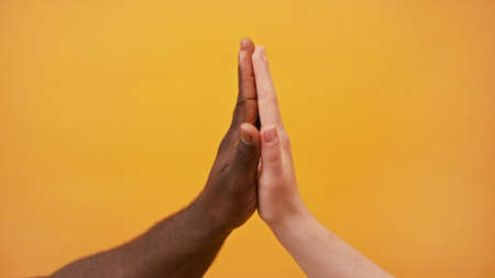 Photo for black and white hands holding together isolated on the orange background. Close up. - Royalty Free Image