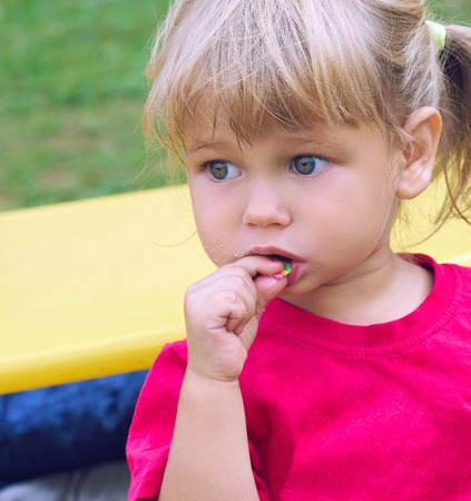 Photo for Cute little Caucasian girl enjoy eating bubble gum at kindergarten playground on beautiful summer day. - Royalty Free Image