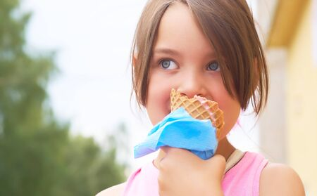 Photo pour Pretty little girl eating licking big ice cream in waffles cone happy laughing on nature background - image libre de droit