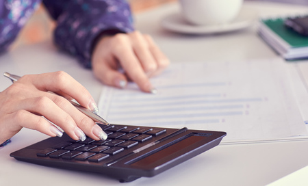 Photo for Close up of female accountant or banker hand making calculations. Savings, finances and economy concept - Royalty Free Image