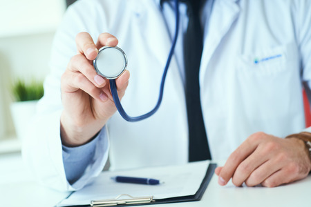 Photo pour Close up of a doctors hand, holding a stethoscope outstretched towards the viewer. Medic shop or store, physical and disease prevention, er consultant, 911, pulse measure, healthy lifestyle concept - image libre de droit