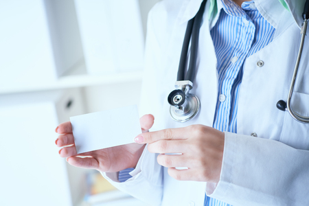 Photo pour Close-up image of female doctor with stethoscope and blank visiting card with place for text in hands. - image libre de droit