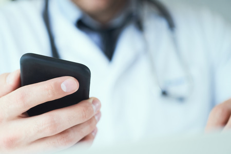 Photo pour Male doctor hands with mobile phone close-up. Male doctor in white coat is using a modern smartphone device with touch screen. - image libre de droit