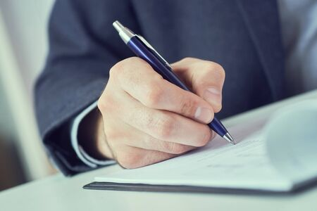 Photo pour Hand of businessman in suit filling and signing with blue pen partnership agreement form clipped to pad closeup. Management training course, some important document, team leader ambition concept. - image libre de droit