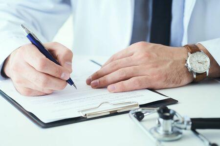 Photo pour Mid section of male doctor writing write prescription to patient at worktable. Panacea and life save, prescribing treatment. - image libre de droit