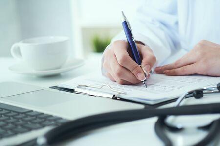 Photo pour Mid section of female doctor writes prescription to patient at worktable. Panacea and life save, prescribing treatment. - image libre de droit