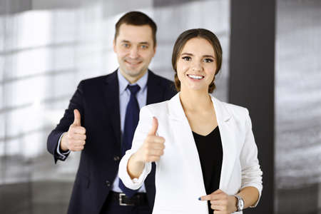 Photo pour Smiling businesspeople are happy with a good result of their teamwork, standing with thumbs up in a modern office. Concept of business success - image libre de droit