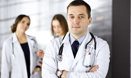 Photo pour Professional middle aged doctor with a stethoscope and crossed arms at work in a clinic. Perfect medical service in a hospital. Medicine and healthcare concept - image libre de droit