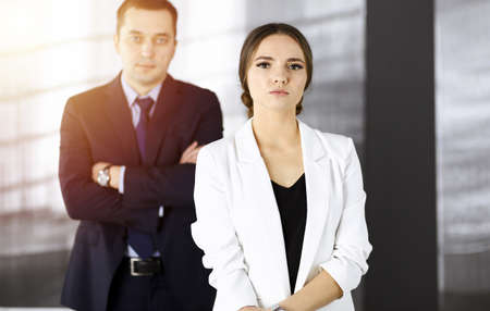 Photo pour Young intelligent businesswoman is standing straight in a sunny modern office with her colleague at the background. Concept of successful business - image libre de droit