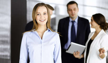 Photo pour Young blonde businesswoman dressed in blouse is standing in a modern office. Concept of success in a business - image libre de droit